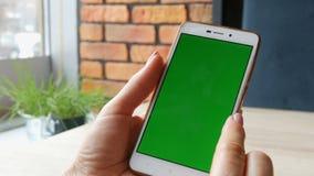 Tela verde Smartphone A chave do croma em um smartphone branco, as mãos fêmeas guarda o telefone celular no café filme