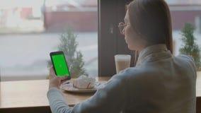 TELA VERDE sobre o tiro do ombro da fêmea caucasiano nova com cabelo preto longo usando o telefone celular com chave do croma vídeos de arquivo