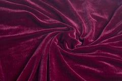 Tela vermelha de veludo com dobras espirais fotografia de stock royalty free