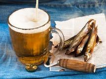 Tela, vetro di birra, pesce salato Fotografia Stock