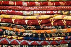 Telas, colchas e lenços turcos brilhantes, coloridos com testes padrões orientais diferentes A textura da matéria têxtil ou da te Imagens de Stock Royalty Free