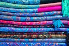 Telas, colchas e lenços turcos brilhantes, coloridos com testes padrões orientais diferentes A textura da matéria têxtil ou da te Fotografia de Stock
