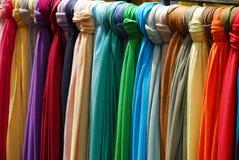 Telas coloreadas brillantes atadas a un carril fotos de archivo libres de regalías