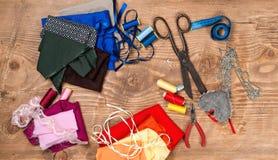 Telas de algodón para coser, la cinta métrica y los accesorios para la costura en el fondo de madera Visión superior Fotos de archivo libres de regalías