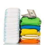 Telas de pila, pañales disponibles y dinero aislados en blanco Imagen de archivo libre de regalías
