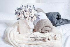 Telas escocesas de Brown, blancas y grises en la cama y las flores foto de archivo