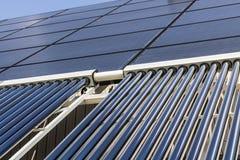 Telas planos térmicos solares com os coletores evacuados do tubo Muitas empresas estão instalando fontes de energia renováveis II fotos de stock royalty free