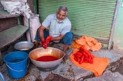 Telas teñidas hombre indio en colores brillantes Imágenes de archivo libres de regalías