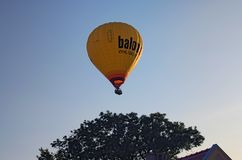 TELC, THE CZECH REPUBLIC-AUGUST 25, 2017: One hot balloon over the big tree and the roof of the house.  Stock Image