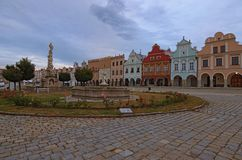 Wide angle cloudy morning landscape of main square of Telc or Teltsch with Plague Column, fountain and renaissance colorful houses stock image