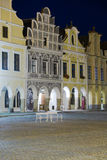 Telc - UNESCO heritage. Illuminated city houses with arcade on square in Telc, Bohemia - Czech Republic, with empty bench during dusk. UNESCO protected heritage Royalty Free Stock Photography
