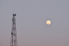 Telco transmission relay tower and moon in evening. A tall country relay tower is silhouetted in in a dusty grey early evening sky. A full moon makes its way Royalty Free Stock Photos
