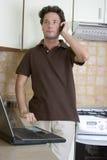 Telearbeit - nach Hause arbeitend in der Küche stockfotografie