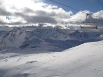 Telecadeira na frente dos picos de montanha cobertos de neve nos cumes Foto de Stock
