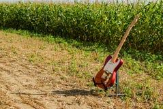 Telecaster de la guitarra en color rojo contra la perspectiva de un campo de maíz encendido imagen de archivo libre de regalías
