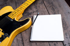 Telecaster with notepad on wood table Royalty Free Stock Photography