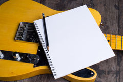 Telecaster with notepad on wood table Stock Photos