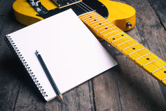 Telecaster with notepad on wood table Royalty Free Stock Photo