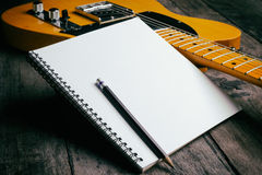 Telecaster with notepad on wood table Royalty Free Stock Photos