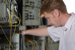 Telecom engineer looks on multiplexer Royalty Free Stock Images