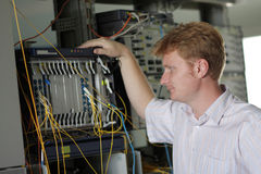 Telecom engineer looks on multiplexer Royalty Free Stock Photography