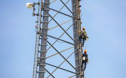 Telecom maintenance. Two repair men climbing on tower against blue sky background. Communication maintenance. Two technicians climbing on telecom tower antenna stock image