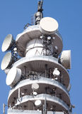 Telecom Tower against a blue sky. Telecom tower with multiple receiving and transmitting dishes against a blue sky Royalty Free Stock Photo