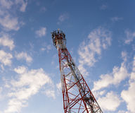 Telecom tower in the evening bright sunlight. And cloudy blue sky Stock Photo