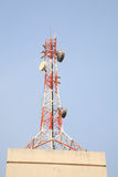 Telecom tower on top of building. Against blue sky Royalty Free Stock Photos