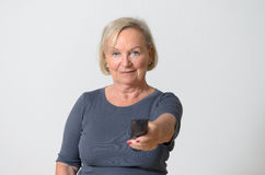 Telecomando della tenuta della donna adulta contro Gray Immagini Stock Libere da Diritti