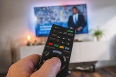 Telecomando della TV, la mano con un telecomando, vista di POV Fotografie Stock Libere da Diritti