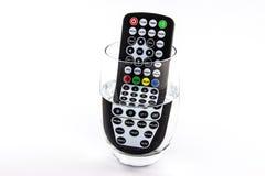 Telecomando impermeabile della TV in un bicchiere d'acqua Fotografia Stock Libera da Diritti