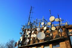 Telecommunicatie en microgolfantennes en schotels op hogere post die van aricable worden geïnstalleerd Avondzonlicht en blauwe he royalty-vrije stock afbeelding