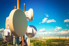 Telecommunicatie-uitrusting met TV-antennes, satellietschotel en microgolfantennes van mobiele exploitanten tegen blauwe sk royalty-vrije stock afbeeldingen