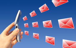 Telecommunication. A picture of a hand holding a mobile phone in the air, with illustrated envelopes flying in/out of the phone Royalty Free Stock Photography