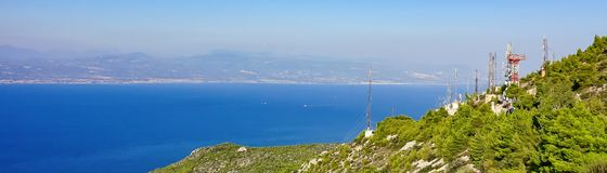 Telecommunication antennas on the edge of a mountain near the sea stock image