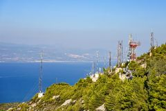 Telecommunication antennas on the edge of a mountain near the sea stock photo
