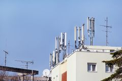 Telecommunication base stations network repeaters on the roof of. The building. The cellular communication aerial on a building roof. Cell phone Stock Images