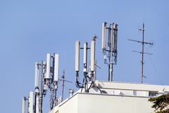Telecommunication base stations network repeaters on the roof of. The building. The cellular communication aerial on a building roof. Cell phone Stock Photos