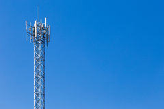 Telecommunication cellular tower against cloudy blue sky Stock Photo