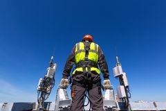 Telecommunication engineer in helmet and uniform holds telecomunication equipment in his hand and antennas of GSM DCS. UMTS LTE bands, outdoor radio units stock photography