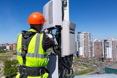 Telecommunication engineer in helmet and uniform installs telecomunication equipment in his hand and antennas of GSM DCS. Telecommunication engineer  in helmet stock photo