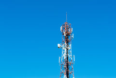 Telecommunication mast television antennas on blue sky Stock Photos