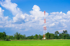 Telecommunication Radio Antenna and Satelite Tower with blue sky. With cloud and green field Stock Photos