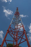 Telecommunication tall tower, white and red and blue sky. Stock Image