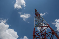Telecommunication tall tower, white and red and blue sky. Stock Photos
