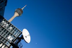 Telecommunication Technologies. The Rhein Tower (Rheinturm) in Düsseldorf, Germany, a very big satellite dish and the Moon Royalty Free Stock Photo