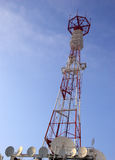 Telecommunication tower. With dish antennas on a cloudy blue sky background Stock Photography