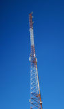 Telecommunication tower. In red and white with blue sky on background Royalty Free Stock Photography