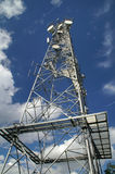 Telecommunication tower. On blue cloudy sky background Royalty Free Stock Images
